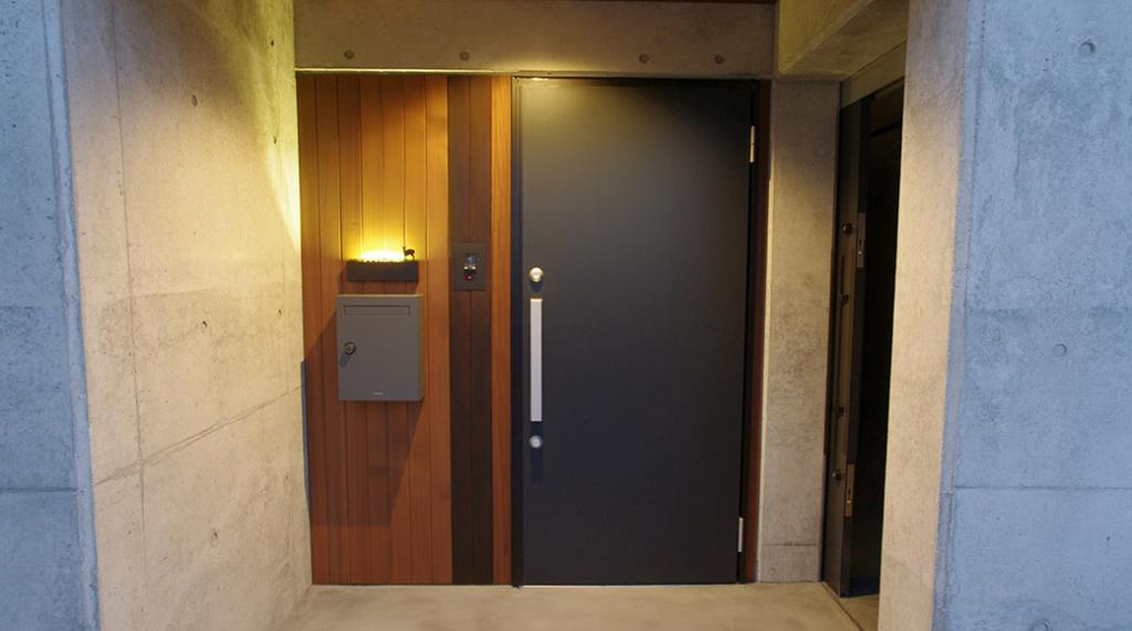 道路すぐ玄関の御宅のため玄関横に照明が埋め込まれたタイプ表札
