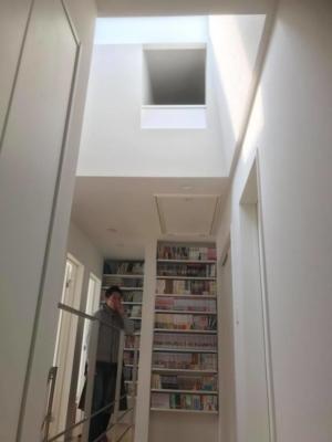 壁一面の本棚と天窓で明るい廊下